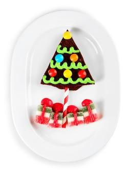 プレート上のおいしいクリスマスクッキーとゼリー、白で隔離