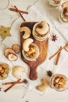 Вкусный десерт из рождественского печенья с запеченным яблоком и сливками на деревянной тарелке на белом столе