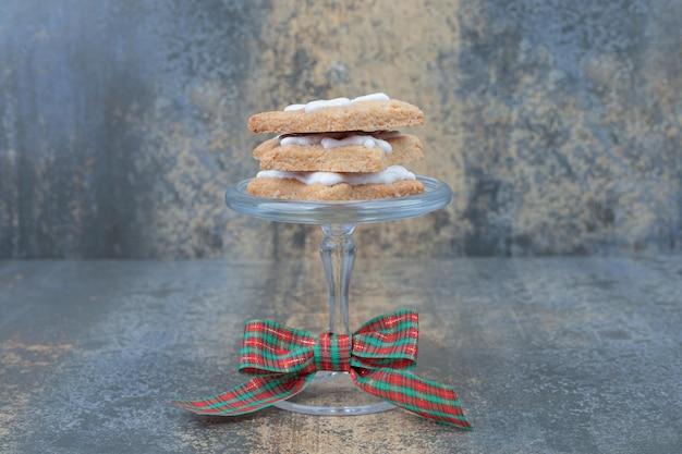 Deliziosi biscotti di natale su lastra di vetro con fiocco sul tavolo di marmo.