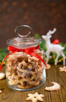 茶色の背景のテーブルの上の瓶においしいクリスマスクッキー