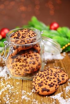 茶色の表面のテーブルの上の瓶においしいクリスマスクッキー