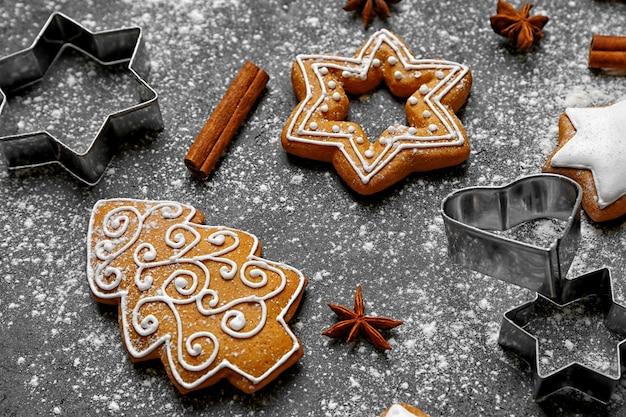 灰色の背景に粉砂糖が散らばったおいしいクリスマスクッキー