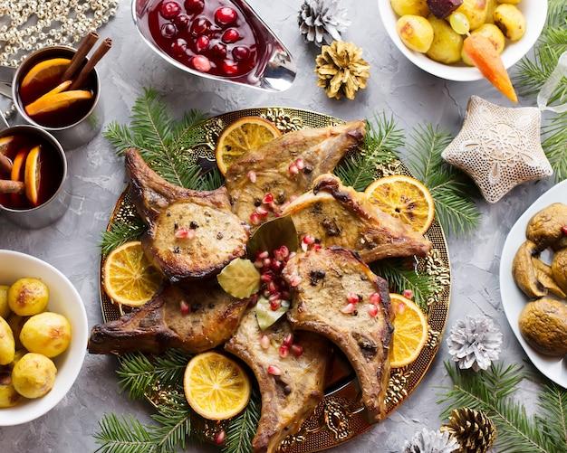 ローストミートステーキ、クリスマスリースサラダ、ベイクドポテト、グリル野菜、クランベリーソースを添えたおいしいクリスマスミール。