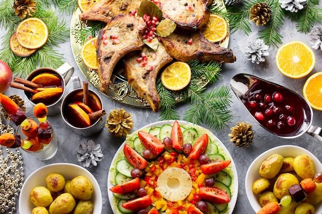 ローストミートステーキ、クリスマスリースサラダ、ベイクドポテト、グリル野菜、クランベリーソースを添えた美味しいクリスマスミール。