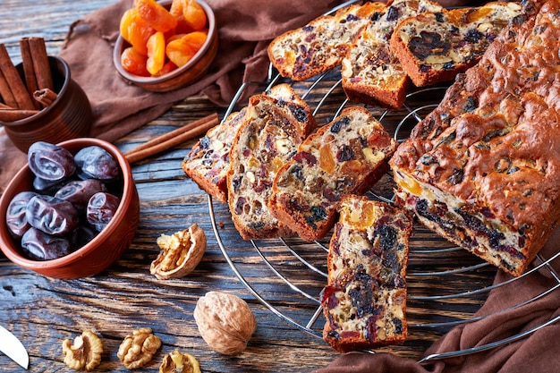 Delicious chunky dried fruits loaf cake on a wire cake stand with brown cloth, cinnamon sticks, dried apricots and date fruits on a rustic wooden table, view from above, close-up