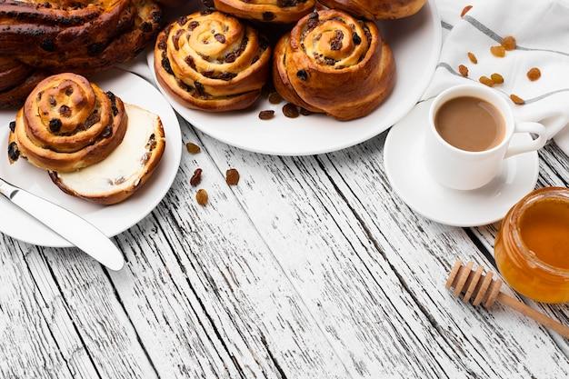 Вкусные булочки с корицей и изюмом на деревянном столе