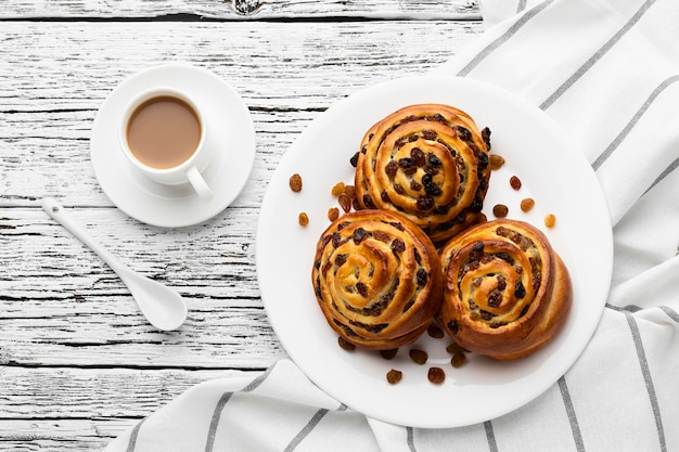 Delicious cinnamon raisins rolls on wooden table