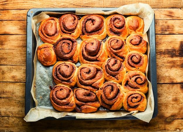 Вкусные булочки с корицей. домашняя корица на тарелке. аппетитные булочки