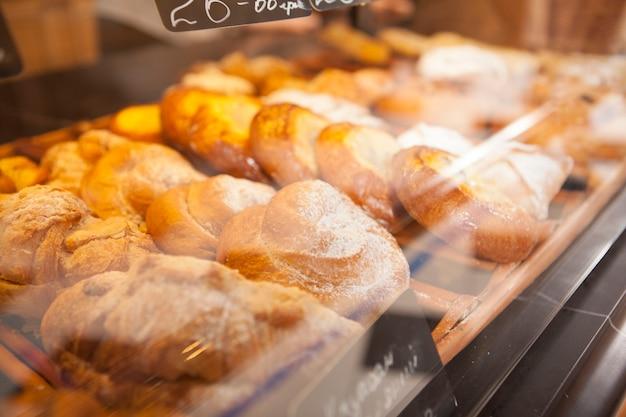 Вкусные булочки с корицей на полке в пекарне