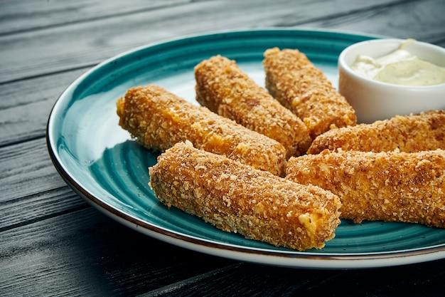 Вкусный крупным планом вид на фритюре рыбы или сырные палочки жареные с белым соусом на синюю тарелку на черном столе. барная закуска к пиву.