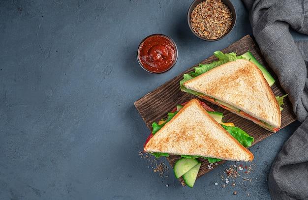 茶色の背景に野菜ハムチーズと揚げトーストのおいしいクラブサンドイッチ