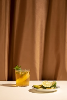 Delicious cocktail drink with mint leaves and lime slices on table in front of brown curtain