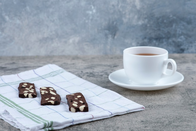 Delicious cocoa bread rusk with nuts and cup of aroma tea on marble surface.