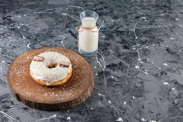 Вкусный кокосовый пончик с шоколадом и стаканом молока на мраморном столе.