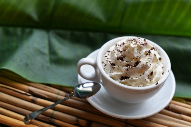 Delicious coffee in a cup with cream on a wooden background