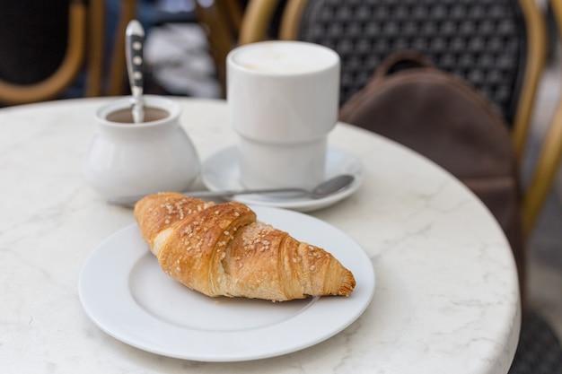 Вкусный кофе с круассаном. концепция французского завтрака. чашка кофе на открытом воздухе стол на террасе кафе