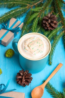 Delicious coffee with foam on new year's day with gifts and fir branches.