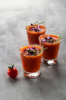 Delicious cold gazpacho soup in glasses on gray background
