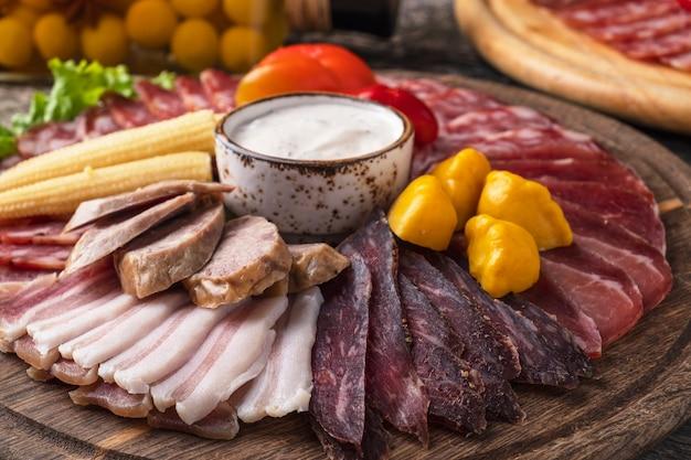 Вкусные холодные закуски с разными сосисками и маринованными овощами на деревянной доске