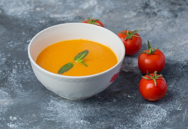 Delicious colored tomato cream-soup with fresh tomatoes on grey table.