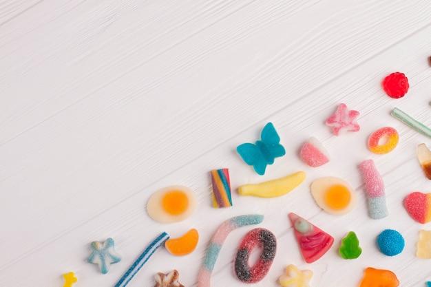 白地に色とりどりの美味しいキャンディー。さまざまな形や色のキャンディー。上面図