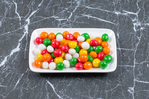 Delicious colorful candies on white plate.
