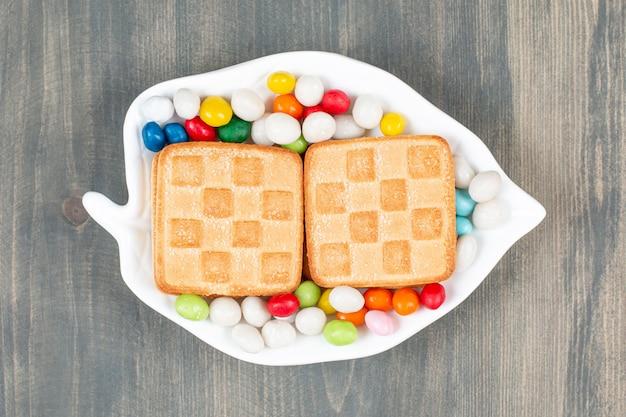 白いプレートにクッキーが入ったおいしいカラフルなキャンディー。高品質の写真