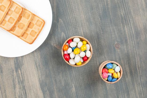 Вкусные красочные конфеты с печеньем на белой тарелке