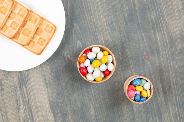 Delicious colorful candies with cookies on a white plate