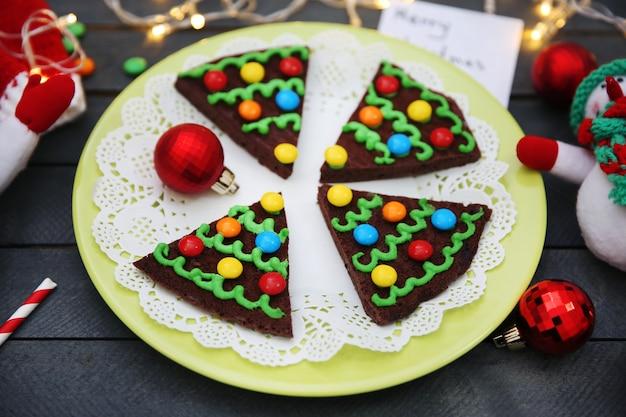 お祝いの装飾が施されたプレート上のおいしいカラフルなクリスマスクッキー