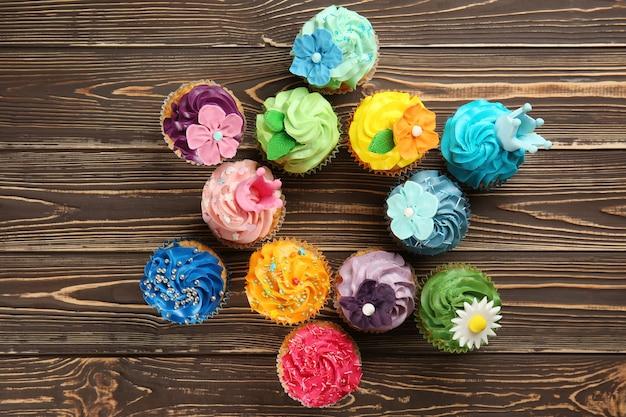 Вкусные красочные кексы на деревянной поверхности