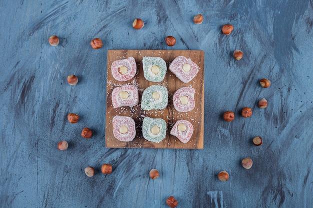Вкусные красочные сладости с орехами на деревянной доске.