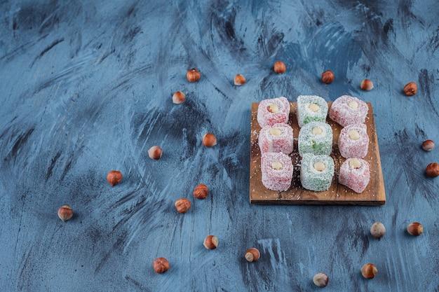 나무 보드에 견과류와 함께 맛있는 다채로운 달콤한 즐거움.