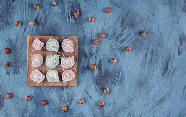 木の板にナッツを添えた、色とりどりのおいしいお菓子。
