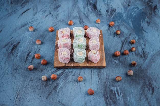 Delicious colorful sweet delights with nuts on wooden board.