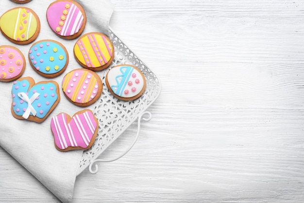 Вкусное красочное пасхальное печенье на подносе и белом деревянном столе