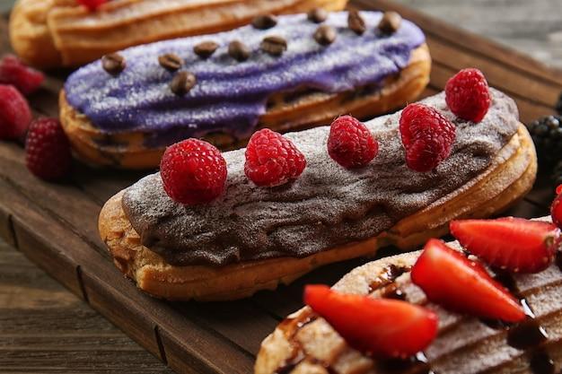 Вкусные красочные эклеры с ягодами на деревянной разделочной доске