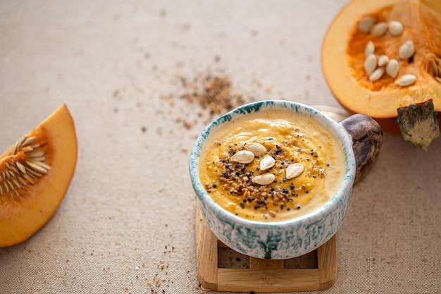 Deliziosa composizione con zuppa di zucca in un bellissimo piatto di ceramica. cibo stagionale.