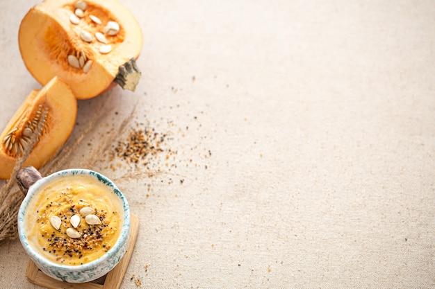 美しいセラミック皿の上面図にカボチャスープを使ったおいしい組成物。旬の食材。