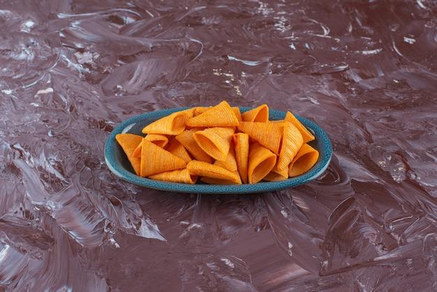 大理石のテーブルの上に、プレートのおいしいコーンチップス。