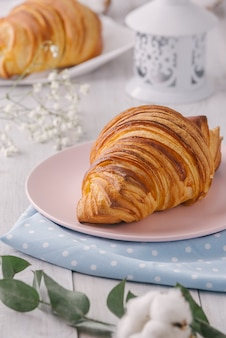 Delicious continental breakfast with fresh flaky french croissants, close up on the croissants. with white cotton flowers. provence rustic style.