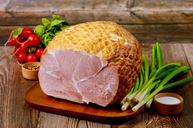 ねぎと大根と木の板で調理されたおいしいハム。