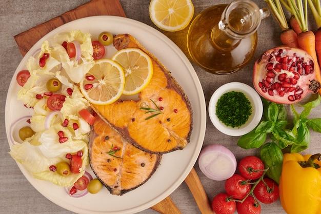 Вкусные приготовленные филе лосося. филе лосося на гриле и салат из свежих овощей и помидоров с зеленым салатом. концепция сбалансированного питания для чистой флекситарной средиземноморской диеты.