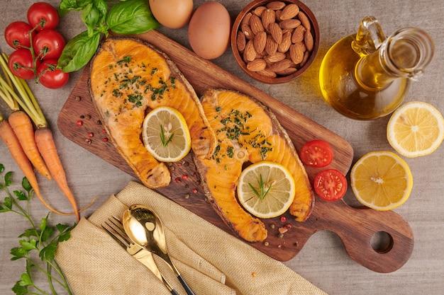 맛있는 요리 연어 생선 필레. 구운 연어 생선 필레와 신선한 녹색 양상추 야채 토마토 샐러드. 깨끗한 식사 flexitarian 지중해 다이어트를위한 균형 잡힌 영양 개념.