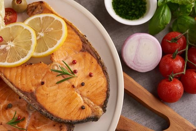 おいしい鮭の切り身。サーモンフィッシュフィレのグリルとフレッシュグリーンレタスの野菜トマトサラダ。準菜食主義の地中海式食事をきれいに食べるためのバランスの取れた栄養の概念。