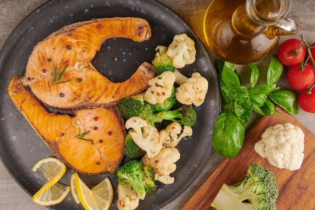 Delicious cooked salmon fish fillets. grilled salmon fish fillet and fresh green lettuce vegetable tomato salad. balanced nutrition concept for clean eating flexitarian mediterranean diet.