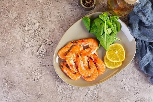 Вкусные приготовленные креветки в тарелке, изолированные на сером фоне. вареные креветки