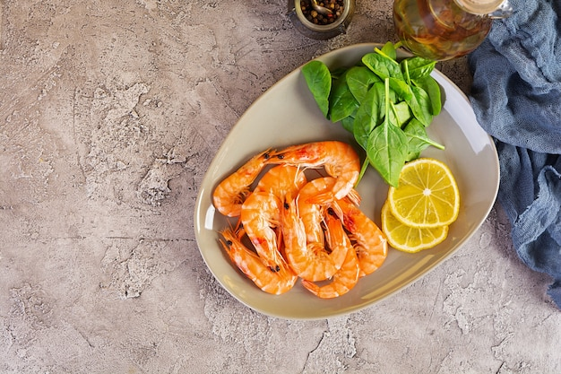 Delicious cooked shrimps in plate isolated on grey background. boiled prawns