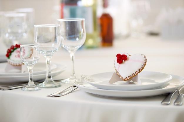 흰색 달콤한 유약으로 덮여 있고 작은 빨간 장미와 흰색 작은 진주로 장식 된 맛있는 쿠키가 테이블 위에 서서 와인 잔과 함께 제공됩니다. 축제 결혼식 테이블을위한 좋은 장식.