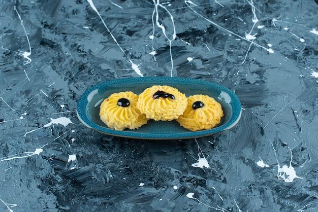 青いテーブルの上に、皿の上においしいクッキー。